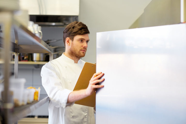 Man in chef whites opens stainless steer refrigerator door.